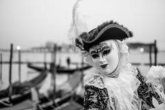 Мужской ходок масленицы в традиционном костюме и маска стоя с назад к грандиозному каналу, гондолам на заднем плане Стоковое фото RF