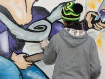 Мужской художник улицы: Распылять на общественной городской стене города Стоковая Фотография