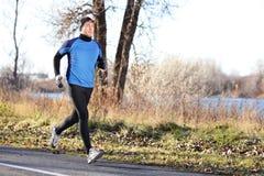 Мужской человек бегуна бежать в осени на холодный день стоковое фото rf