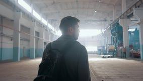 Мужской человек менеджера идя в большой современный склад с задней частью к телезрителю сток-видео