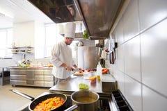 Мужской шеф-повар варя еду на кухне ресторана Стоковая Фотография