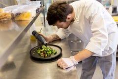 Мужской шеф-повар варя еду на кухне ресторана Стоковые Фотографии RF