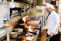 Мужской шеф-повар варя с горящими пламенами стоковое фото rf