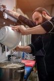 Мужской шеф-повар в черной равномерной варя сливк стоковые изображения