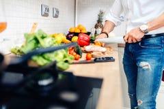 Мужской шеф-повар подготавливая обедающий с куриной грудкой и режа овощи Стоковое фото RF