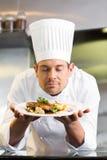 Мужской шеф-повар с глазами закрыл пахнуть еду в кухне стоковое изображение