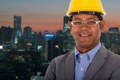 Мужской шлем желтого цвета носки инженера с предпосылкой света города стоковое изображение rf