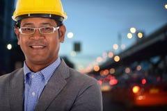 Мужской шлем желтого цвета носки инженера с предпосылкой света города стоковые фотографии rf
