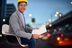 Мужской шлем желтого цвета носки инженера с предпосылкой света города стоковая фотография