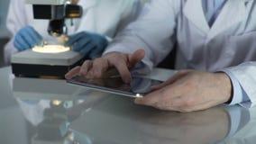 Мужской экран таблетки скроллинга ученого, коллега работая с микроскопом близрасположенным акции видеоматериалы