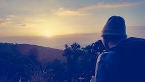 Мужской backpacker принимая фотоснимок на заход солнца в утре Стоковое фото RF