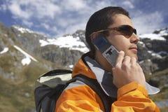 Мужской Hiker используя мобильный телефон против гор стоковые изображения rf