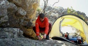 Мужской hiker кладя вверх по шатру в сельскую местность 4k акции видеоматериалы