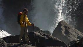 Мужской hiker наблюдает большой водопад в замедленном движении видеоматериал