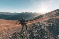 Мужской hiker ослабляя на заходе солнца на саммите горы и смотря величественную панораму итальянских Альпов с скрещиванием грязно стоковые изображения rf