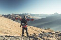 Мужской hiker ослабляя на заходе солнца на саммите горы и смотря величественную панораму итальянских Альпов с скрещиванием грязно стоковое фото rf