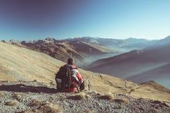 Мужской hiker ослабляя на заходе солнца на саммите горы и смотря величественную панораму итальянских Альпов с скрещиванием грязно стоковая фотография rf