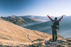 Мужской hiker ослабляя на заходе солнца на саммите горы и смотря величественную панораму итальянских Альпов с скрещиванием грязно стоковая фотография