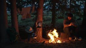 Мужской hiker отдыхая около костра в лагере леса напольное воссоздание акции видеоматериалы