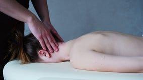 Мужской masseur с сильными руками замешивает шею молодой женщины которая лежит на кресле в светлой комнате косметологии акции видеоматериалы