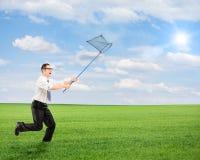 Мужчина бежать с пустой сетью бабочки на поле Стоковая Фотография RF