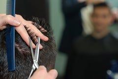 Мужчина волос вырезывания парикмахера конца-вверх Стоковая Фотография
