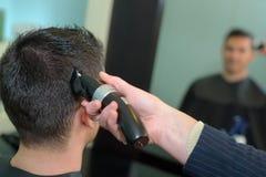 Мужчина волос вырезывания парикмахера с клипером волос Стоковые Фотографии RF
