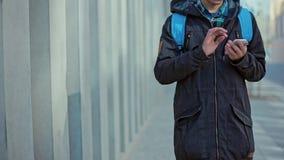 Мужчина вручает удары на телефоне Outdoors на холодный день акции видеоматериалы