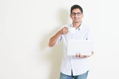 Мужчина вскользь дела индийский используя компьютер и выпивая чай Стоковые Фотографии RF