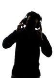 Мужчина в силуэте слушая к наушникам Стоковая Фотография