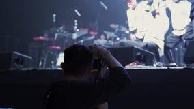 Мужчина держит камеру и принимает видео танцуя группы в составе молодые активные люди на этапе сток-видео