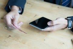 Мужчина держа кредитную карточку и используя умный мобильный телефон для onli стоковая фотография rf