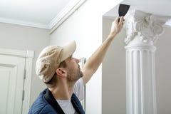 Мужчина держит нож замазки на стене около угла стены Стоковые Изображения