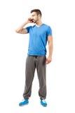 Мужчина детенышей подходящий в sweatpants говоря на телефоне Стоковые Фото