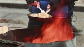 Мужчина жарит еду на лотке, зиму outdoors, пластичная вилка, бедный человек сток-видео