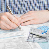 Мужчина заполняя вне налоговую форму 1040 США - один против одного коэффициент Стоковые Изображения RF