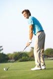 мужчина игрока в гольф с teeing Стоковое Изображение RF