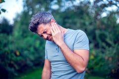 Мужчина имея боль уха касаясь его тягостное головное внешнему стоковые изображения rf