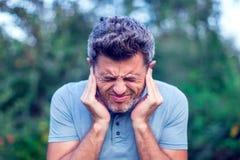 Мужчина имея боль уха касаясь его тягостное головное внешнему стоковое изображение rf