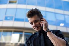 Мужчина испытал главный исполнительный директор говоря через мобильный телефон, стоя outdoors против компании стоковое изображение