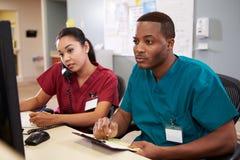 Мужчина и женская медсестра работая на станции медсестер Стоковая Фотография