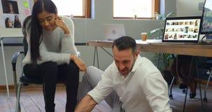 Мужчина и женские график-дизайнеры обсуждая над фотоснимками 4k сток-видео