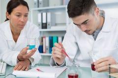Мужчина и женские медицинские или научные исследователя в лаборатории Стоковые Фотографии RF