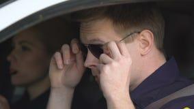 Мужчина и женские патрульные офицеры кладя на стекла, подготавливая для патрулировать видеоматериал