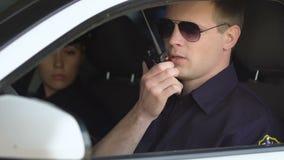 Мужчина и женские полисмены сидя в патрульной машине признавая звонок появления, принуждение акции видеоматериалы