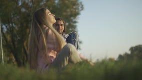 Мужчина и женские сидят на озере видеоматериал