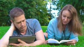 Мужчина и женщина читают в парке акции видеоматериалы