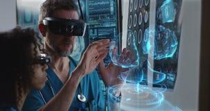 Мужчина и сканирование мозга женского доктора рассматривая видеоматериал
