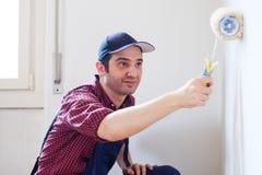 Мужчина крася его стены дома белизны с роликом стоковые фото