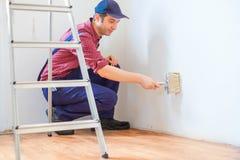 Мужчина крася его стены дома белизны с щеткой стоковое фото rf